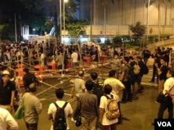 10月13日晚上,數以百計佔中支持者在金鐘道從中銀大廈至警察總部長達150米的路段上加固多處路障。(美國之音記者海彥攝)