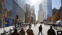 Pedestrians walk along Greenwich Street next to 4 World Trade Center (L) in New York, Nov. 13, 2013.