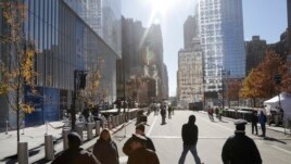 Pedestrians walk along Greenwich Street next to 4 World Trade Center (L) in New York, Nov. 13, 2013.
