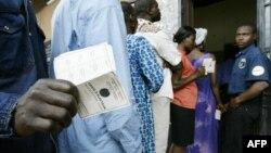 Un homme montre sa carte d'électeur à l'extérieur d'un bureau de vote dans la capitale Yaoundé le 11 octobre 2004.