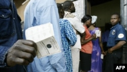 Un homme montre sa carte d'électeur à l'extérieur d'un bureau de vote dans la capitale Yaoundé, le 11 octobre 2004.