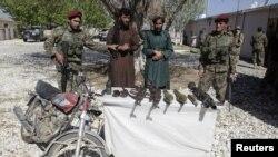 Pemberontak Taliban yang tertangkap dan senjata mereka di propinsi Ghazni (26/4).