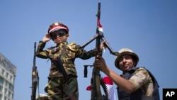 Un niño en uniforme de soldado saluda junto a un militar a bordo de un vehículo blindado que vigila la entrada a la plaza de Tahir, en El Cairo.