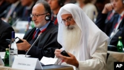 Participants plug in their translator devices during the opening of an international conference on religious and ethnic minorities being persecuted under the Islamic State group, in Paris, France, Sept. 8, 2015.