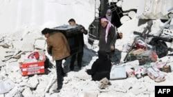 Warga mengeluarkan kompor gas dari gedung yang hancur menyusul serangan udara di Aleppo, Suriah (6/2). (AFP/AMC/Fadi Al-Halabi)