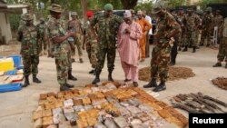 Nigerian military officials stand near ammunition seized from suspected members of Hezbollah after a building raid, Kano, May 30, 2013.