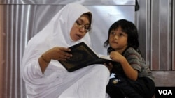 Seorang perempuan membacakan Al-Quran kepada anaknya di sebuah sore di Masjid Istiqlal, Jakarta (foto: dok).