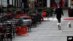 Arhiva - Žena šeta pse pored prazne bašte kafića u centru Begrada, 26. marta 2020. (Darko Vojinović, AP foto)