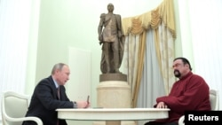 Tổng thống Nga Vladimir Putin (trái) cầm hộ chiếu Nga trước khi trao cho diễn viên Mỹ Steven Seagal trong một cuộc gặp tại Điện Kremlin, Nga, ngày 25 tháng 11, 2016.