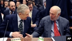 FILE - Soros Fund Management chairman George Soros, left, shakes hands with Renaissance Technologies President James Simons on Capitol Hill in Washington.