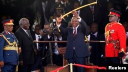 Kenya's President Uhuru Kenyatta (C) displays the special sword that he received to represent his instruments of power from his predecessor, Mwai Kibaki (2nd L), after his official swearing-in ceremony at Kasarani Stadium in Nairobi, April 9, 2013.