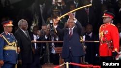 Uhuru Kenyatta (au c.) montre l'épée qu'il a reçue de son prédécesseur Mwai Kibaki comme l'un des symboles du pouvoir