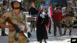 15일 이집트에서 개헌 국민투표가 이틀째 실시된 가운데, 카이로의 투표소에서 한 여성이 군부를 지지하는 구호를 외치고 있다.