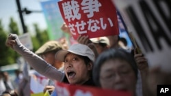 "Hundreds of people stage a rally outside the Japanese Prime Minister's Office in Tokyo, May 14, 2015, protesting a set of controversial bills intended to expand Japan's defense role at home and internationally. A banner, top, reads ""No War."""