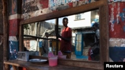 FILE - Pedestrians are reflected in the mirror of a street barber shop in Freetown, Sierra Leone.