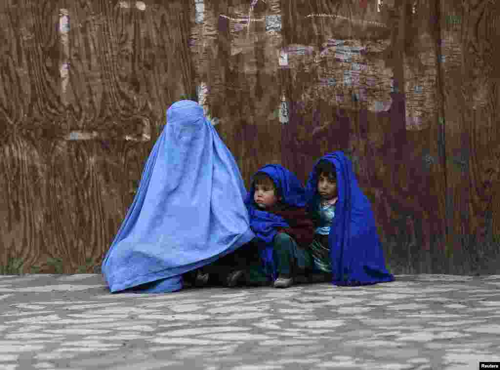 An Afghan woman waits for transportation with her children on a cold day in Kabul.