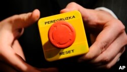 "In 2009, U.S. Secretary of State Hillary Clinton gave Russian Foreign Minister Sergei Lavrov a fake 'reset' button during a meeting in Geneva, Switzerland. The red button says ""reset"" in English and ""overload"" in Russian. This references the Obama administration's desire to improve ties with Russia. (AP Photo / Fabrice Coffrini Pool)"
