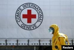 Seorang petugas mengenakan alat pelindung saat ikut dalam konvoi truk desinfeksi Komite Palang Merah Internasional (ICRC) dan Perserikatan Bangsa-Bangsa (PBB). (Foto: dok).