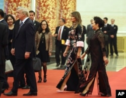 U.S. President Donald Trump, accompanied by U.S. first lady Melania Trump, second from right, and Chinese first lady Peng Liyuan, right, arrives for a state dinner at the Great Hall of the People in Beijing, Nov. 9, 2017.