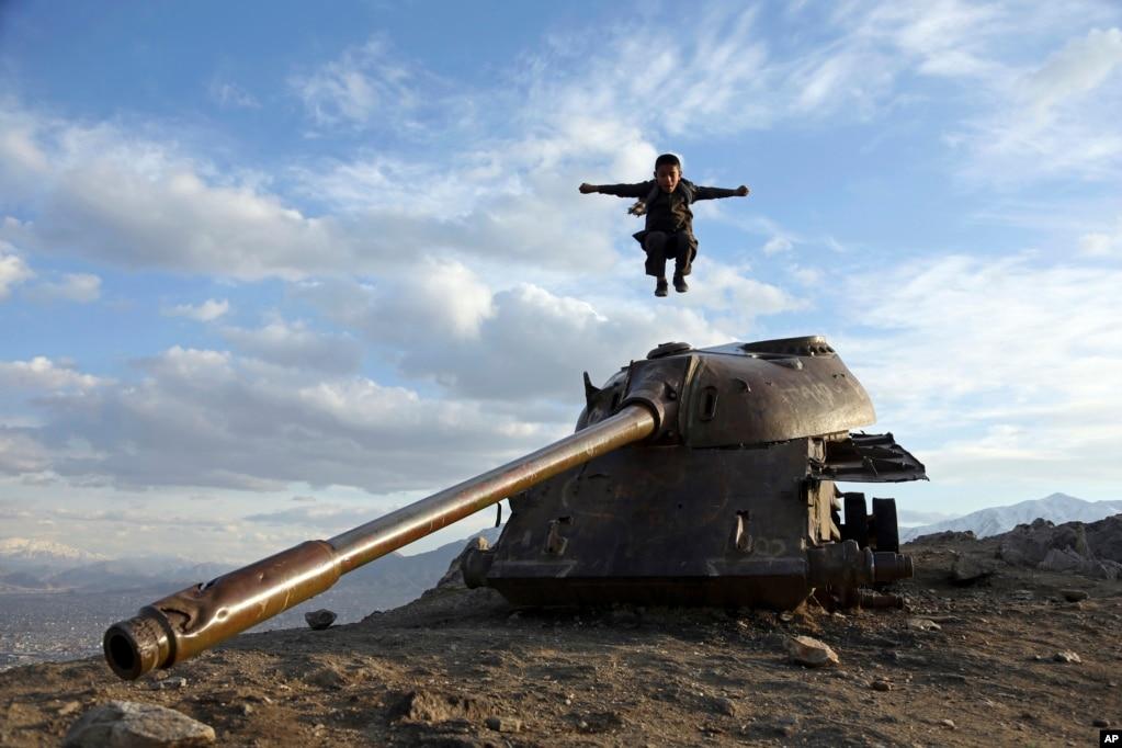 아프가니스탄 카불 외곽의 언덕 꼭대기에 있는 소련군 탱크 포탑에서 한 소년이 힘차게 뛰어내리고 있다.