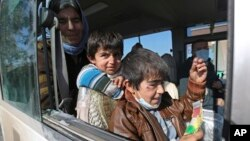 Two Yazidi boys, suffering from several infections from mosquito bites while held by the Islamic State group, wait with their mother inside a bus before being driven to the Kurdish city of Dohuk, in Alton Kupri, outside Kirkuk, Iraq, Jan. 18. 2015.