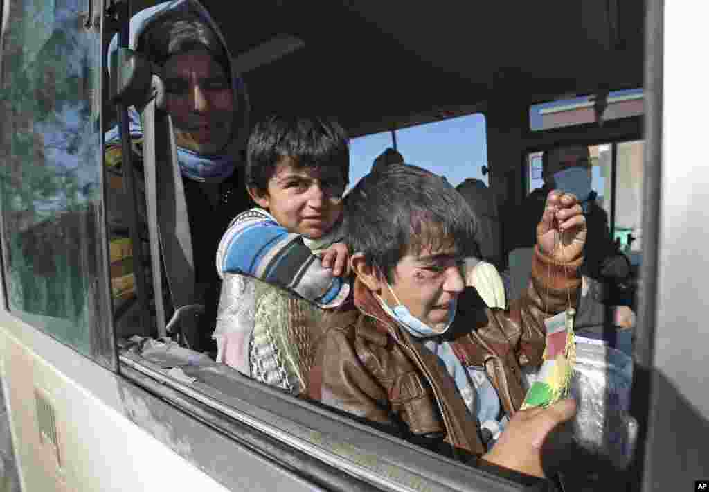 Two Yazidi boys, suffering from several infections from mosquito bites while held by the Islamic State group, wait with their mother inside a bus before being driven to the Kurdish city of Dohuk, in Alton Kupri, outside Kirkuk, Iraq. The Islamic State group released about 200 Yazidis, mostly elderly, held for five months in Iraq.
