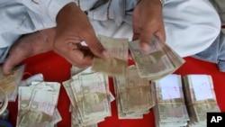 A Pakistani money changer counts Pak rupees in Karachi, Pakistan on Oct 24, 2008.