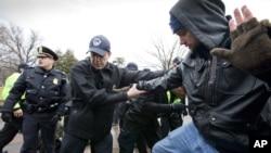 國會山警察將一名'佔領國會山'的示威者驅離西草坪。