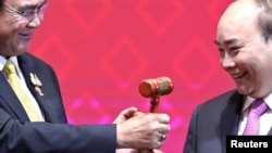 Vietnam's Prime Minister Nguyen Xuan Phuc takes the gavel from Thai Prime Minister Prayuth Chan-Ocha who hands over the ASEAN chairmanship to Vietnam during the closing ceremony of the 35th ASEAN Summit and related summits in Bangkok, Thailand,…