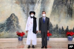 Menlu China Wang Yi (kanan) saat menerima Kepala Politik Taliban, Mullah Abdul Ghani Baradar di Tianjin, China, 28 Juli 2021.