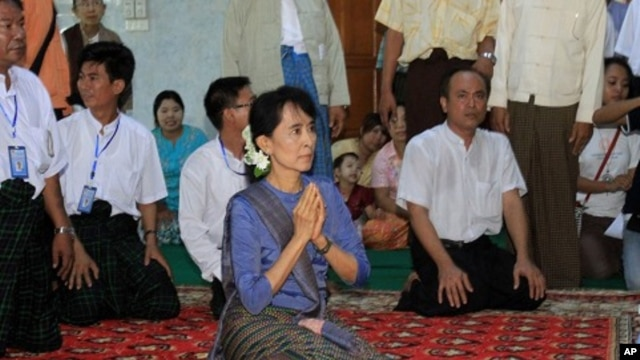 Burmese democracy icon Aung San Suu Kyi, center, pays her respects to a senior Buddhist monk during her visit to a Buddhist monastery in Bago, north of Rangoon, Burma, August 14, 2011
