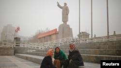 2017年3月23日數名維吾爾族人坐在位於中國新疆維吾爾自治區喀什市中國已故的毛澤東主席雕像附近。