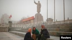 Ethnic Uighurs sit near a statue of China's late Chairman Mao Zedong in Kashgar, Xinjiang Uighur Autonomous Region, China, March 23, 2017.