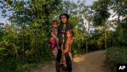 یک زن مسلمان روهنگیایی دختر و پسر خود را در بغل گرفته و آنان به دلیل منازعه در میانیمار، به غذای کافی دسترسی ندارند