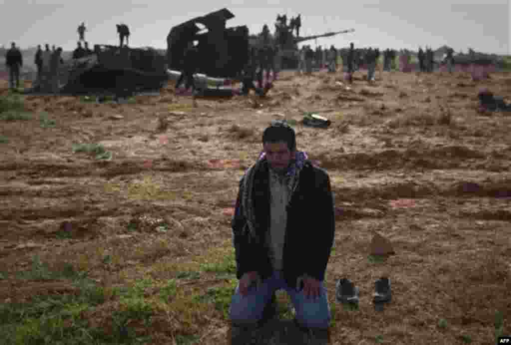 A Libyan man prays in front a destroyed tank on the outskirts of Benghazi, eastern Libya, Sunday, March 20, 2011. The U.S. military said 112 Tomahawk cruise missiles were fired from American and British ships and submarines at more than 20 coastal target