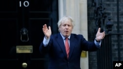 """Britain's Prime Minister Boris Johnson applauds on the doorstep of 10 Downing Street in London during the weekly """"Clap for our Carers"""" Thursday, May 28, 2020. The COVID-19 coronavirus pandemic has prompted a public display of appreciation for care…"""