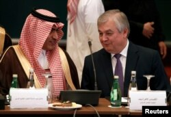 Saudi Gulf Affairs Minister Thamer Al-Sabhan, left, speaks with Russian special presidential envoy for Syria Alexander Lavrentiev during a Syrian opposition meeting in Riyadh, Saudi Arabia, Nov. 22, 2017.