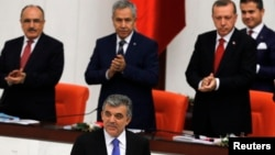 Turkey's President Abdullah Gul (C) is applauded by Prime Minister Tayyip Erdogan (R) and his ministers as he arrives to address the Turkish Parliament during a debate marking the reconvene of the parliament after a summer recess in Ankara, Oct. 1, 2013.