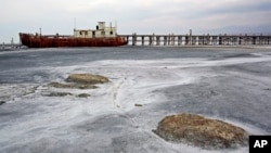 FILE - An abandoned ship is stuck in solidified salt at Lake Urmia, northwestern Iran. Once one of the biggest saltwater lakes on Earth, Urmia has been decimated by climate change, irrigation use and damming of nearby rivers.