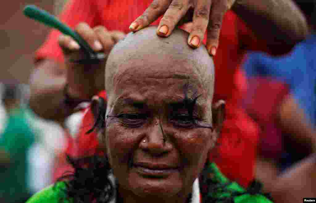 A supporter of Tamil Nadu Chief Minister Jayalalithaa Jayaraman gets her head shaved near Jayalalithaa's burial site in Chennai, India.
