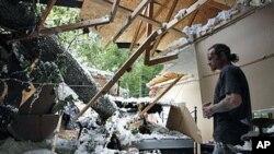 马里兰州一位居民在检查在飓风中被大树砸倒的房屋