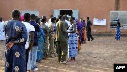 People wait in line to cast their ballots in a polling station in Ouagadougou during Burkina Faso's legislative and municipal elections, December 2, 2012.