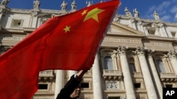 FILE - A pilgrim waves a Chinese flag during Pope Francis weekly general audience in St. Peter square at the Vatican, Nov. 22, 2017.