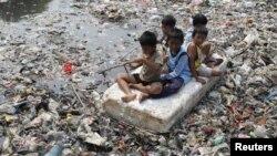 Anak-anak bermain di atas sungai yang penuh sampah di daerah kumuh di Jakarta. (Foto: Dok)