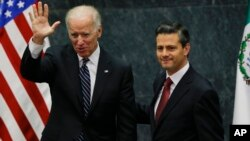 Vice President Joe Biden, left, waves accompanied by Mexico's President Enrique Pena Nieto after delivering a message to the press.
