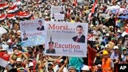 Phất cờ Ai Cập và giương biểu ngữ, hàng vạn người biểu tình tuần hành dưới sức nóng mùa hè hô khẩu hiệu 'Morsi là Tổng thống của chúng ta' và 'Ai Cập là Hồi giáo.' (AP Photo/Hussein Malla)