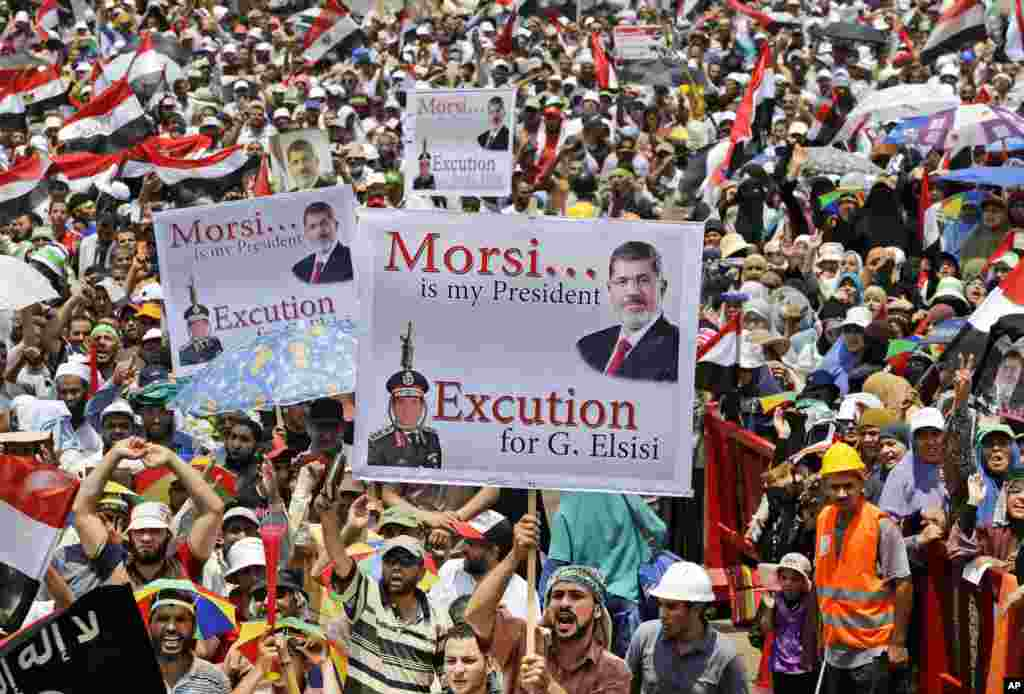 Supporters of Egypt's ousted President Mohammed Morsi hold up placards as they shout slogans during a demonstration where protesters have installed their camp, at Nasr City, Cairo, Egypt, July 19, 2013.