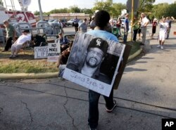 مردی عکسی از مقتول را پیش از مراسم اعدام یکی دیگر از قاتلان به نام «لورنس راسل بریر» حمل میکند.