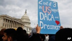 FILE - A woman holds up a sign outside the Capitol in support of the Deferred Action for Childhood Arrivals program, Dec. 5, 2017.