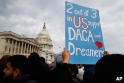 FILE - A woman holds up a sign outside the Capitol in support of the Deferred Action for Childhood Arrivals (DACA) program, Dec. 5, 2017, on Capitol Hill in Washington.